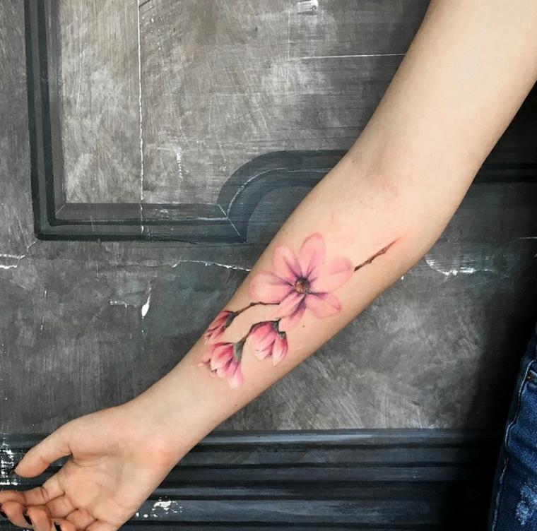 Tatuaggi piccoli particolari femminili, donna con un tattoo colorato di fiori di colore rosa