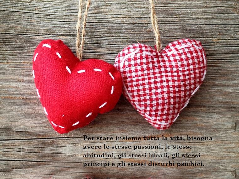Aforismi sull'amore, citazione sotto i due cuori rossi di stoffa con filo di canapa