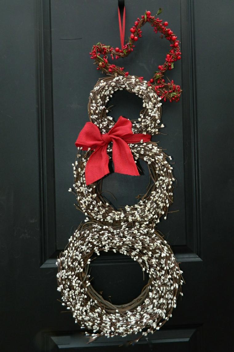 Decorare la porta d'ingresso con un festone di rametti e bacche rosse