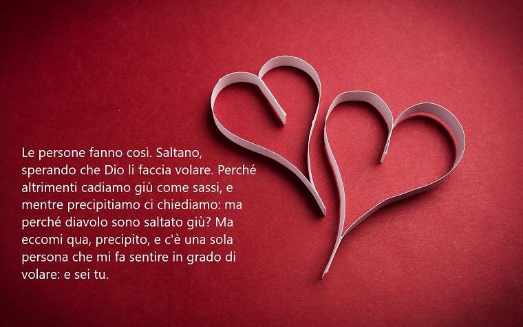 Frasi belle, citazione romantica con una scritta di colore bianco su uno sfondo rosso con due cuori di carta