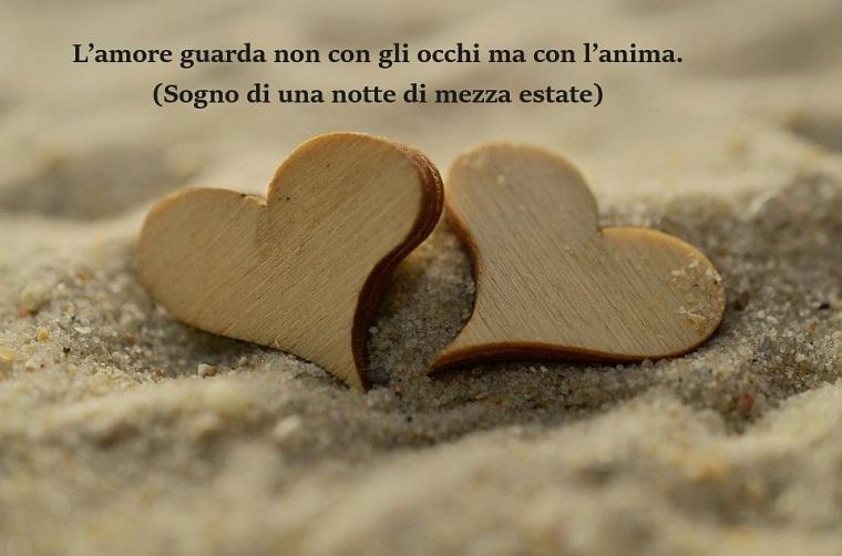 Pensieri d'amore tratti da Sogno di una notte di mezza estate, due cuori in legno sulla sabbia