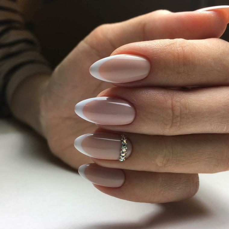 Idea decorazione unghie con una french manicure di color pelle e bianco, accent nail con brillantini sul dito anulare