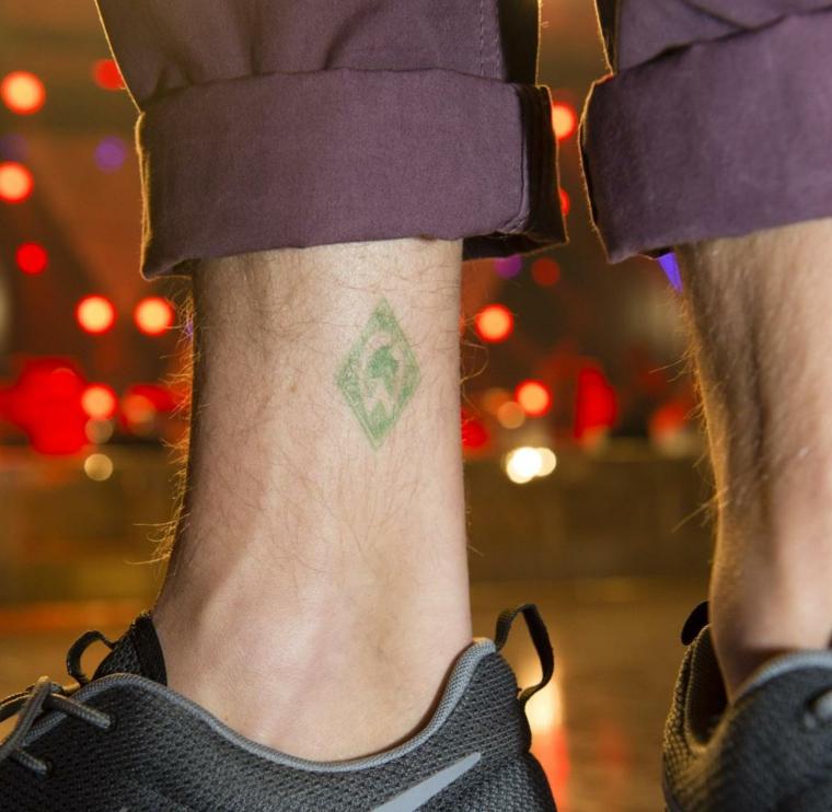 Tatuaggi alla caviglia, tattoo colorato per uomo, scarpe da ginnastica maschili e pantalone viola