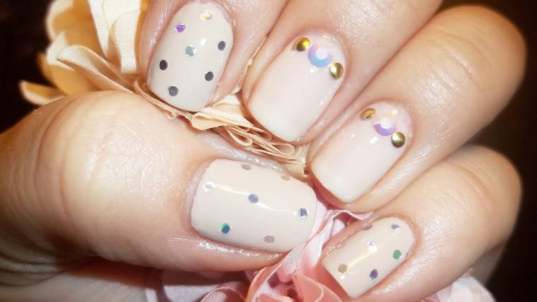 unghie rosa antico chiare con delle decorazioni a pois e delle applicazioni dorate