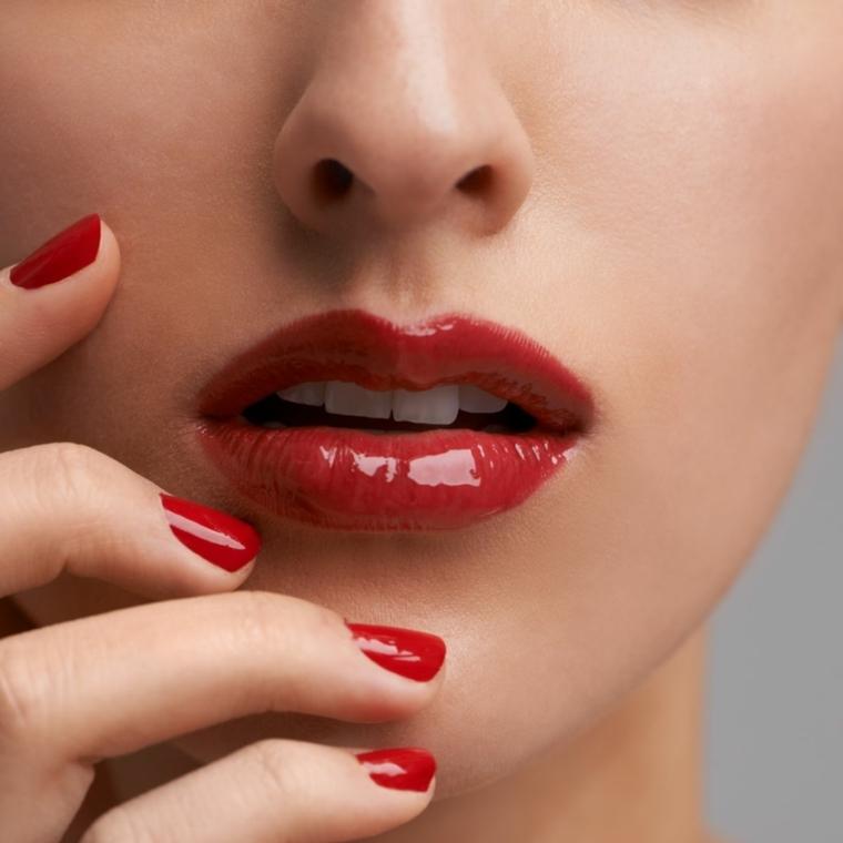 unghia rosse, una manicure a tinta unita con finitura laccata come il rossetto