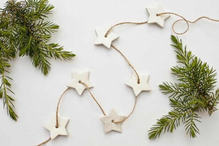 Decorazioni natalizie, ghirlanda fai da te con stelline di pasta fimo e rami di un sempreverde