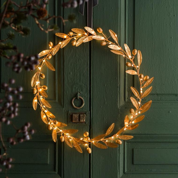 Idea per decorare la porta d'ingresso con un festone di metallo color oro e lucine