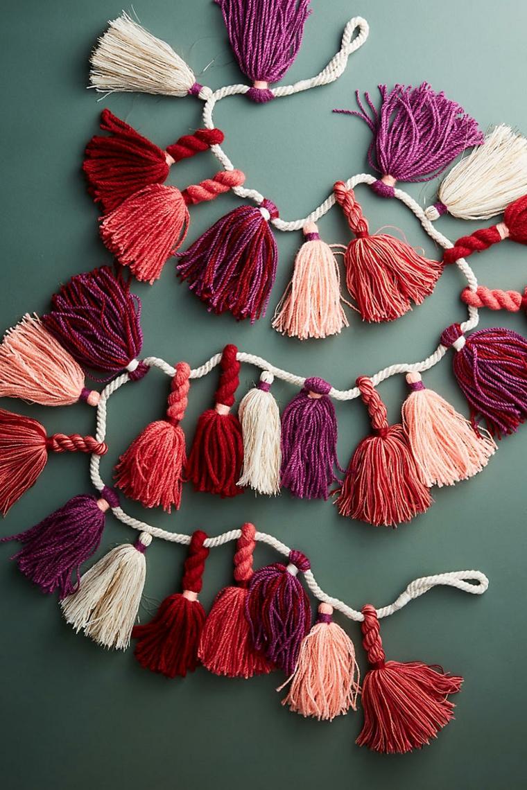 Addobbi natalizi fai da te, una ghirlanda con pon pon di diverso colore su una corda bianca