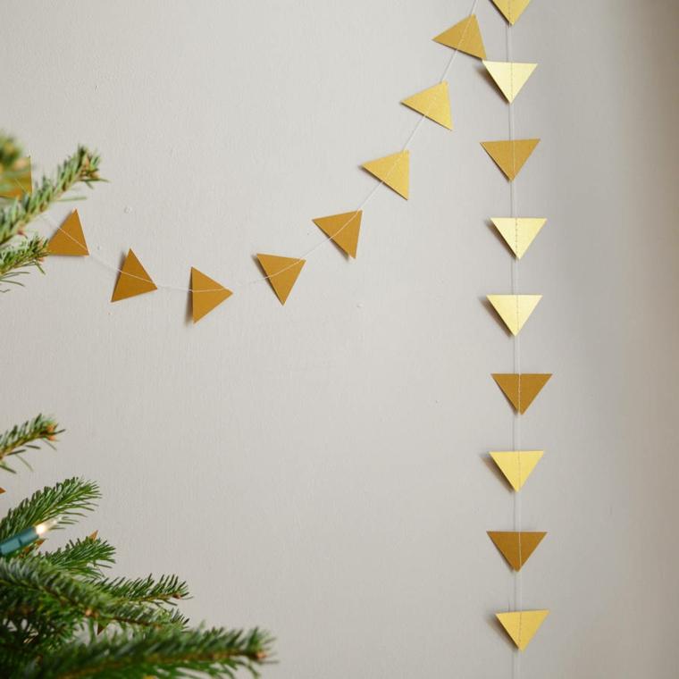 Lavoretti creativi, ghirlanda fai da te con della carta color oro ritagliata a forma di triangolo attaccate su un filo