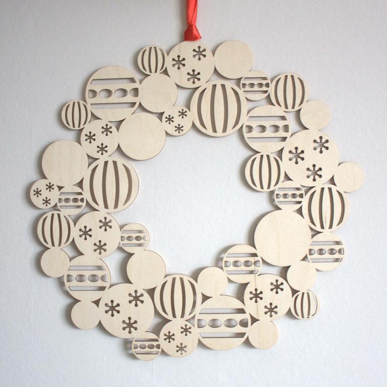 Decorazioni di Natale con una ghirlanda di legno con palline intarsiate e filo rosso per appendere
