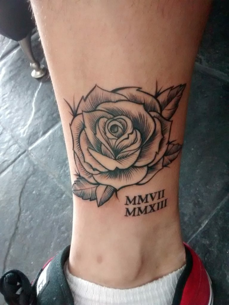 splendida rosa in bianco e nera con una data in numeri romani: idea per un tattoo sulla caviglia