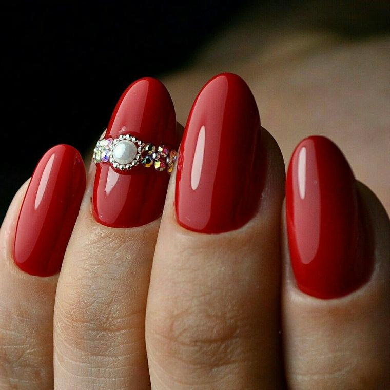 una manicure elegante e chic per il periodo di natale con uno smalto rosso lucido e una decorazione preziosa sull'anulare