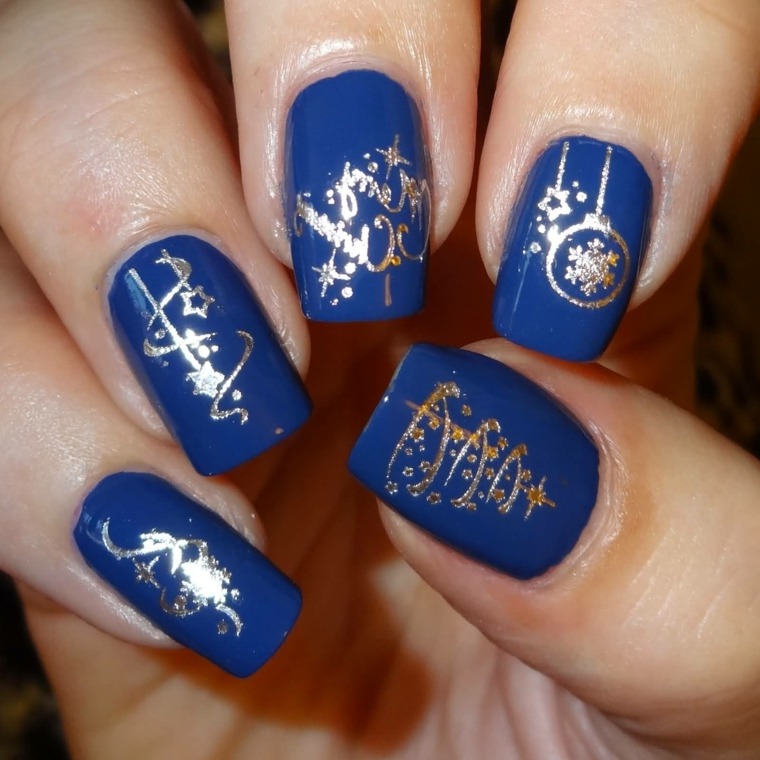 manicure delle feste che gioca sull'abbinamento blu-oro, con scritte e decorazioni