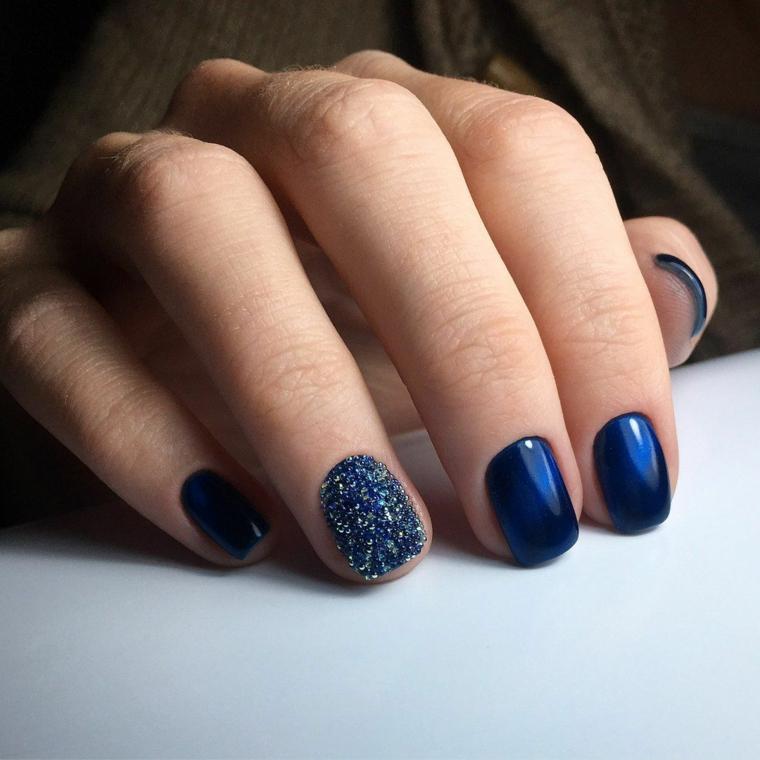 proposta semplice ma molto elegante per la manicure di natale con smalto blu e anulare glitterato