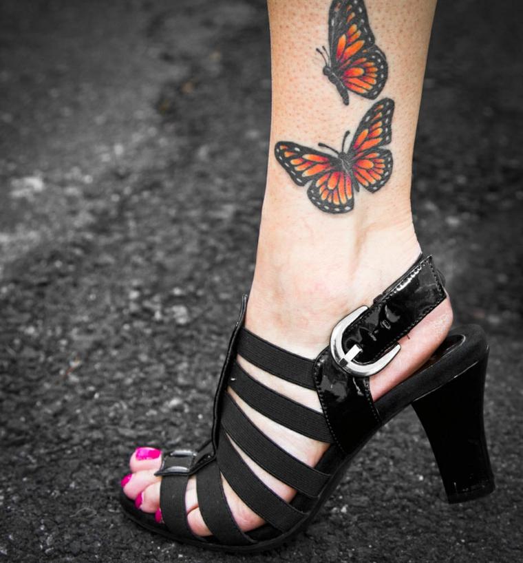 tatuaggio con due farfalle colorate di rosso e giallo sopra la caviglia