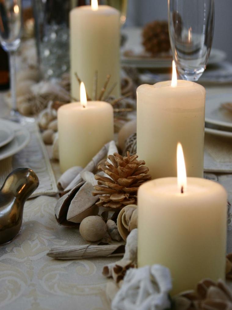 Centrotavola con candele e pigne, tovaglia di colore beige con motivi natalizi