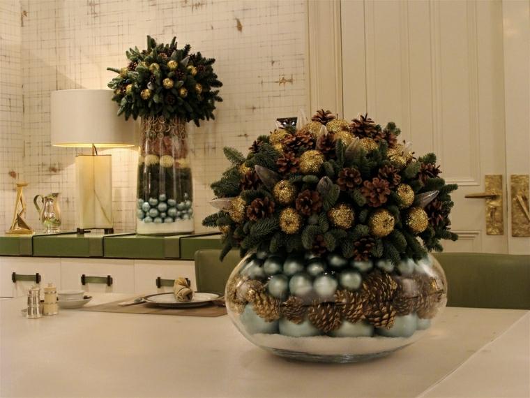 Composizione per il tavolo da pranzo con un vaso grande di vetro, palline color argento e pigne dorate