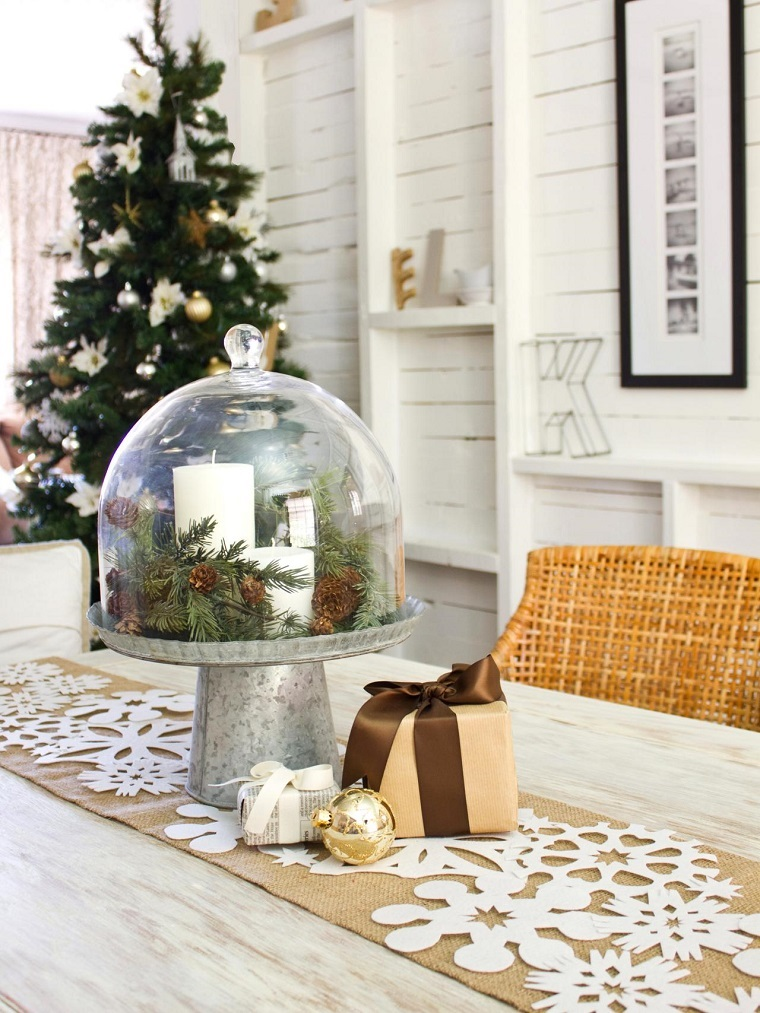Tavola di Natale, centrotavola di vetro con pigne e rametti, pacco regalo e pallina color oro