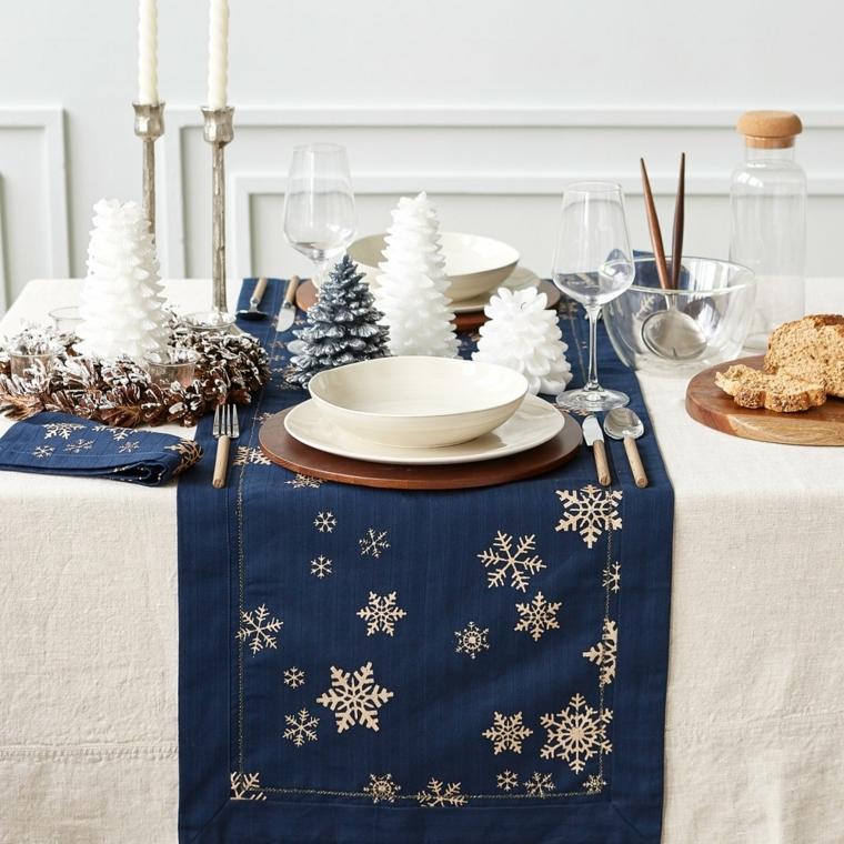Tavola di Natale, decorazioni con alberi piccoli di colore bianco, tovaglia bianca con un runner blu