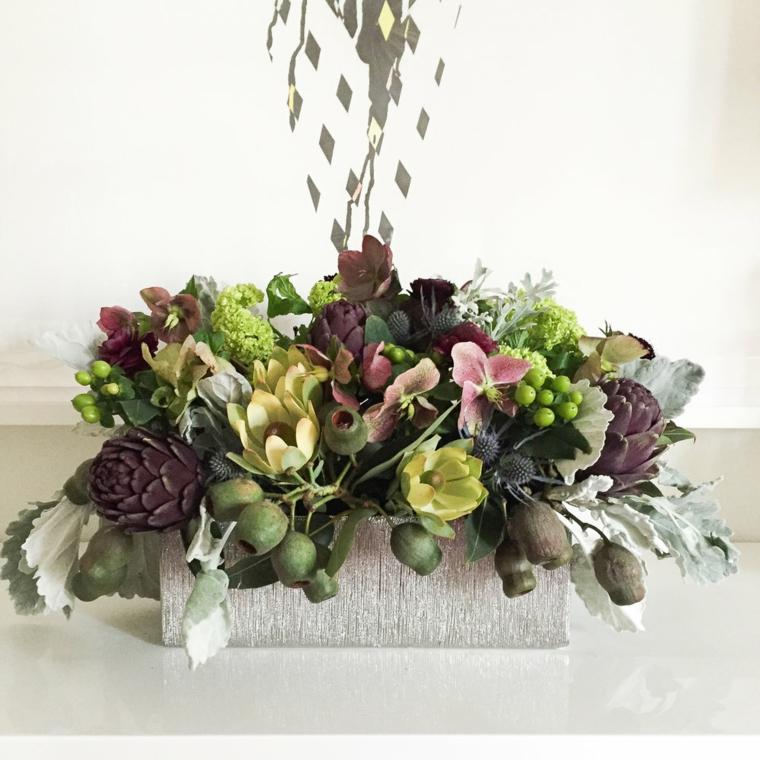 Composizione floreale con un contenitore in legno e tanti fiori come centrotavola