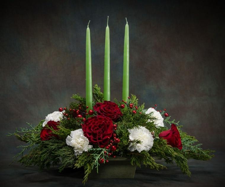 Composizione floreale con rami di un albero di Natale e candele alte di colore verde