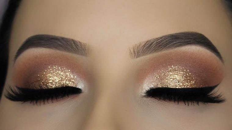 ombretto oro glitterato, con sfumature realizzate con il bianco e il marrone, eye liner e rimmer neri