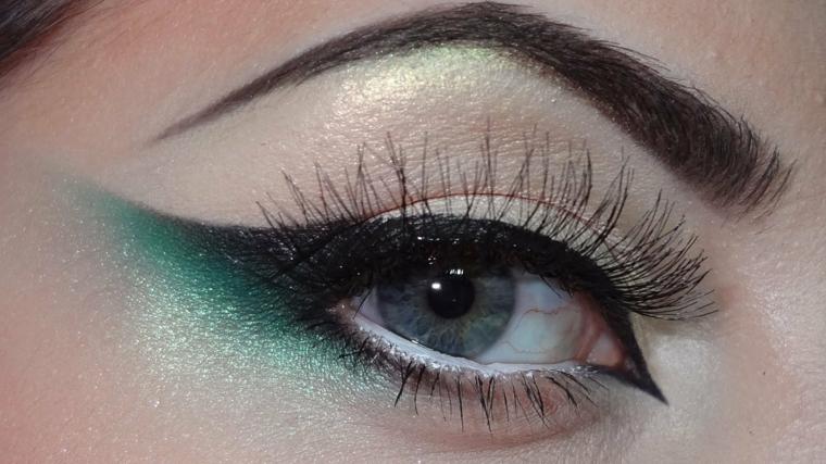 truccare gli occhi otilizzando dell'ombretto verde brillante e della matita nera per allungare l'occhio