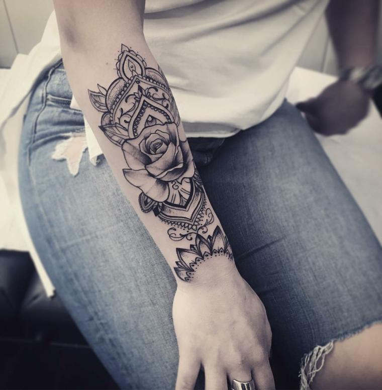 Disegno bello di un mandala sul braccio di una donna, tatuaggio di colore nero con sfumature