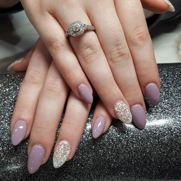 Unghie a forma di mandorla, smalto di colore viola molto chiaro e decorazione pizzo di colore bianco sull'unghia dell'anulare