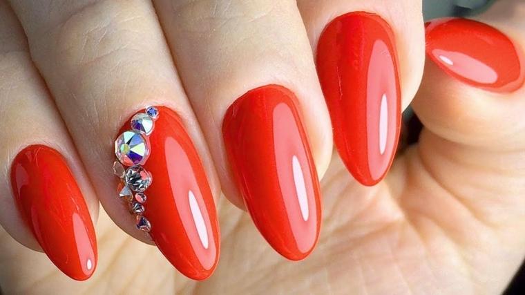 manicure realizzata con uno smalto in gel di una tonalità di rosso chiaro e dei glitter
