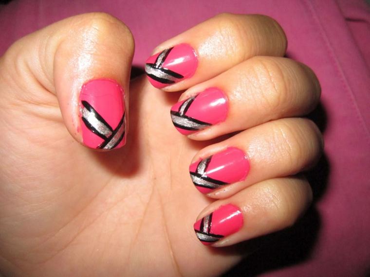 manicure colorata realizzata con uno smalto di una nuance di rosa acceso e decorazioni in nero e argento