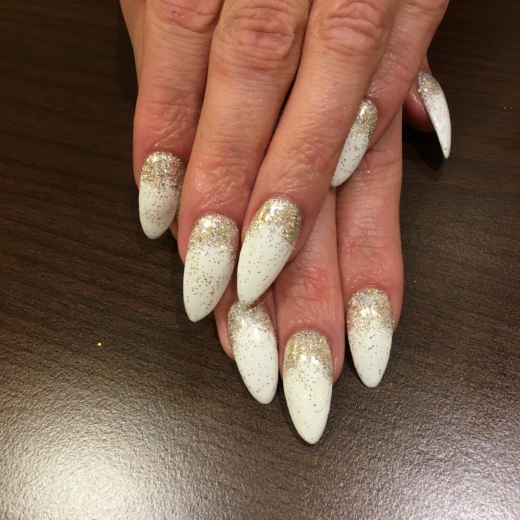manicure per natale, una proposta con unghie molto lunghe e appuntite con smalto bianco e polvere d'oro