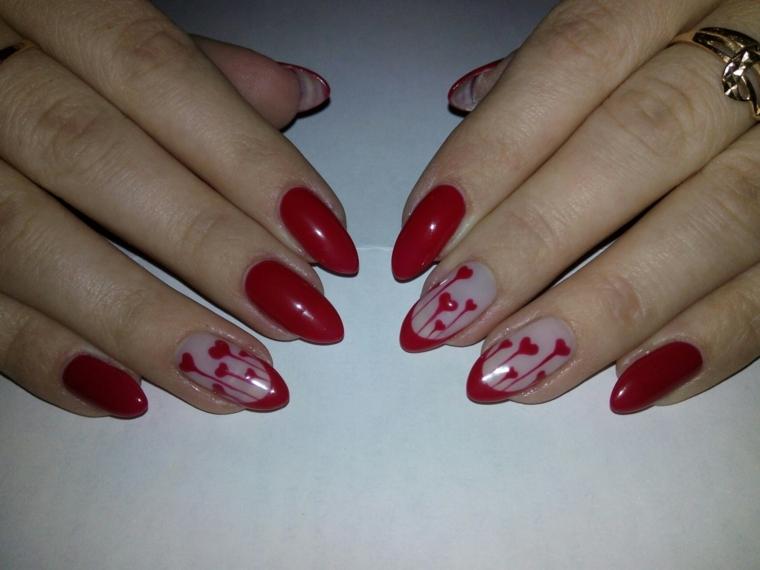 gel rosso, unghie a mandorla dipinte di rosso scuro con anulare e medio decorati con dei cuori