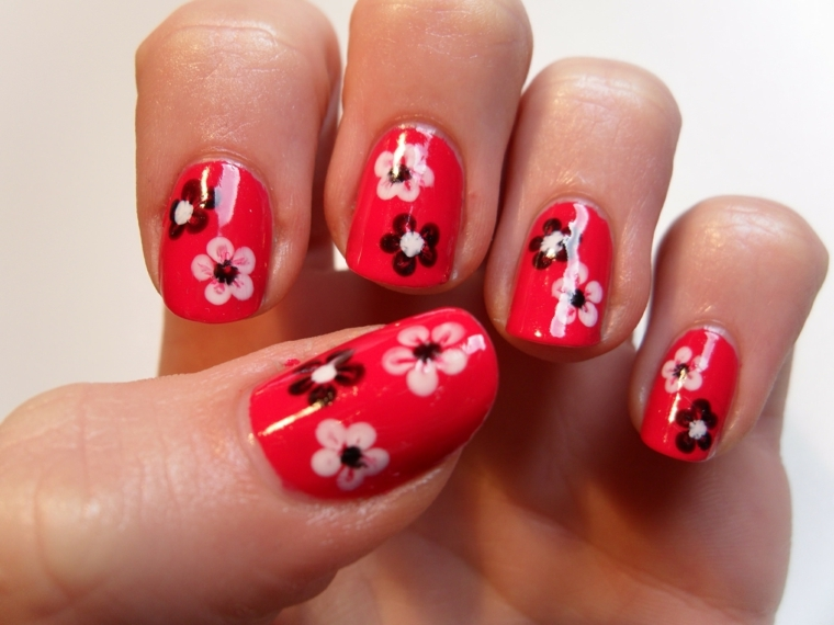 unghie rosse decorate, una proposta con dei piccoli fiori bianchi e neri