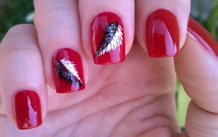 unghie in gel rosse con anulare e medio decorati con una piuma nera e argento