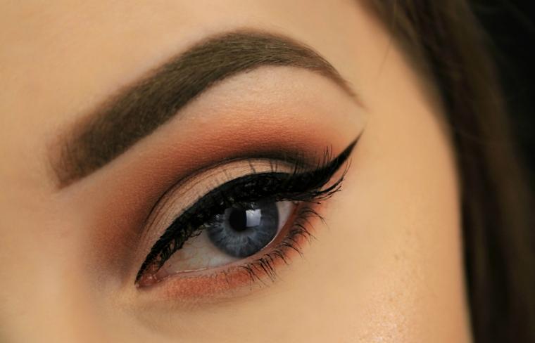 trucco per gli occhi blu realizzato con dell'ombretto dai toni caldi e dell'eye liner nero