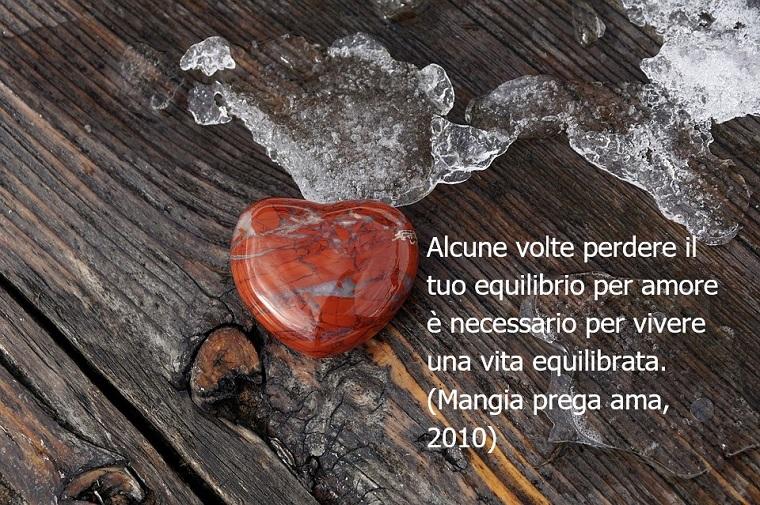 Frasi film e una tratta da Mangia prega ama dell'anno 2010, sfondo in legno con uno cuore di sasso