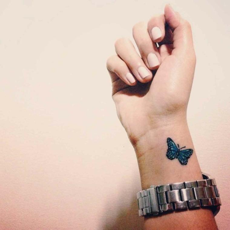 Tattoo farfalla di colore blu con bordi di colore nero sul polso della mano di una ragazza