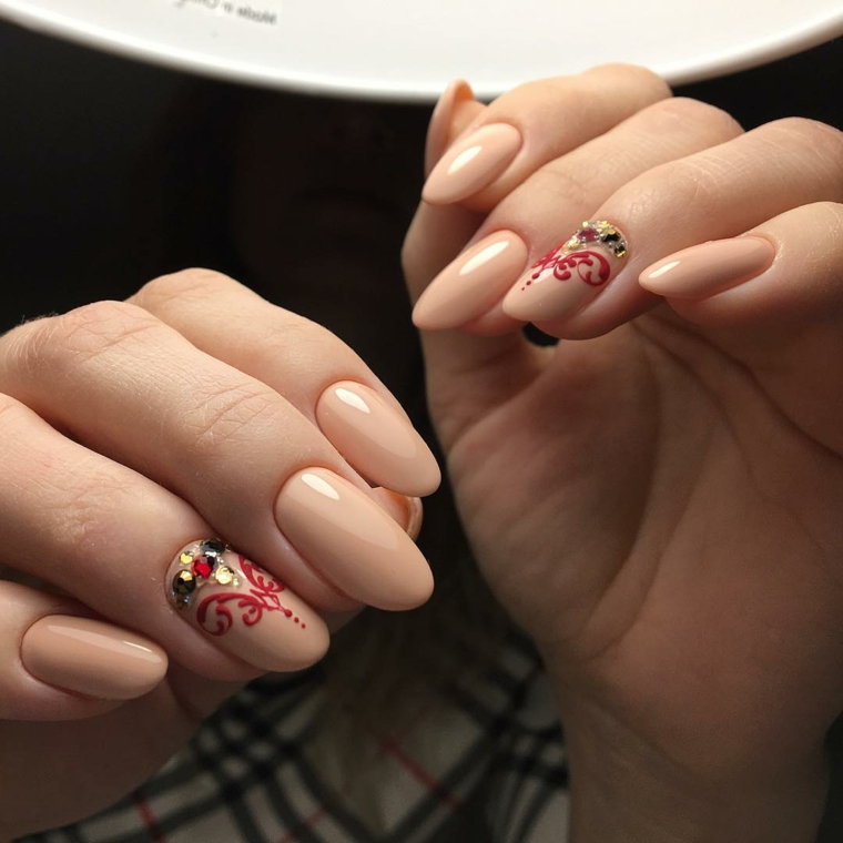 Smalto gel di colore beige, decorazione unghia del dito anulare con brillantini e disegno rosso