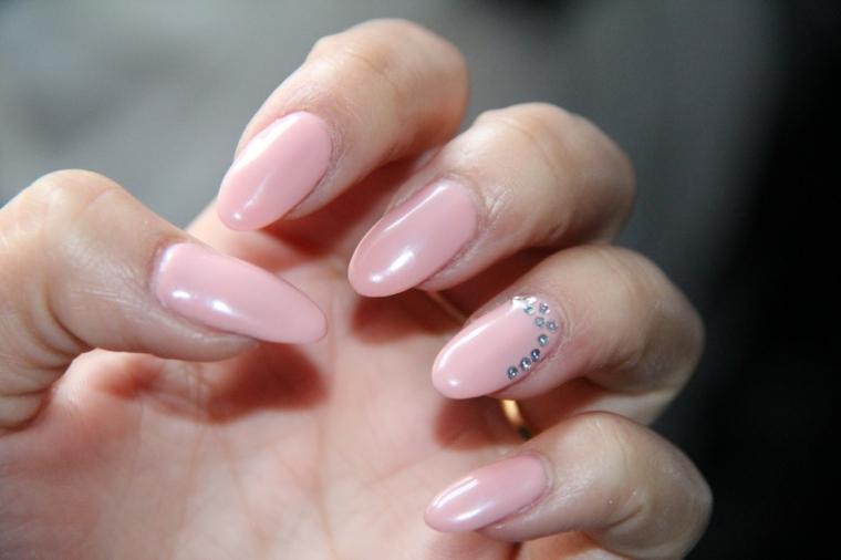 Nail art unghie a punta, smalto gel color pelle con decorazione brillantini sul dito anulare