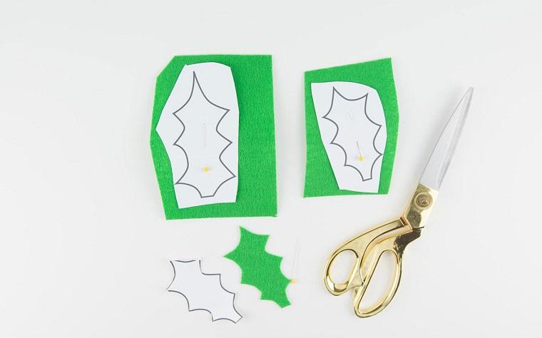 ritagliare con forbici foglie di feltro verde ghirlande natalizie fatte a mano
