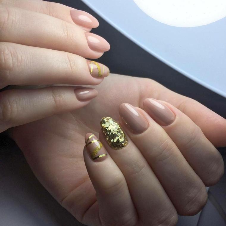 Accent nail sull'unghia del dito anulare con pailettes color oro e nastri sul mignolo su una base smalto beige