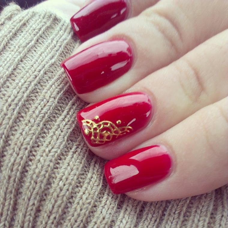 unghie dipinte con uno smalto rosso rosso brillante e anulare decorato con un disegno dorato