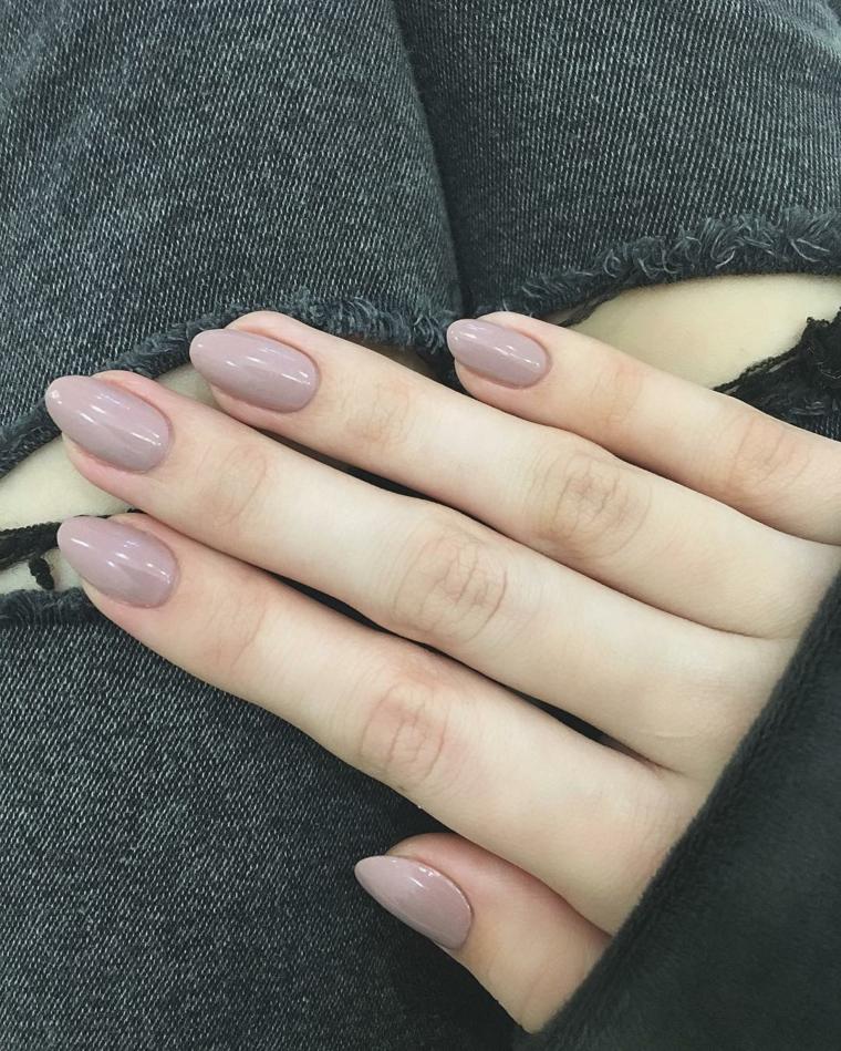 Decorare le unghie di colore beige a forma di mandorla di media lunghezza