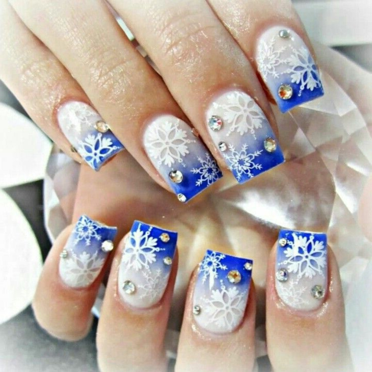 idea per la manicure delle feste realizzata con uno smalto gel bianco e azzurro, fiocchi di neve e glitter