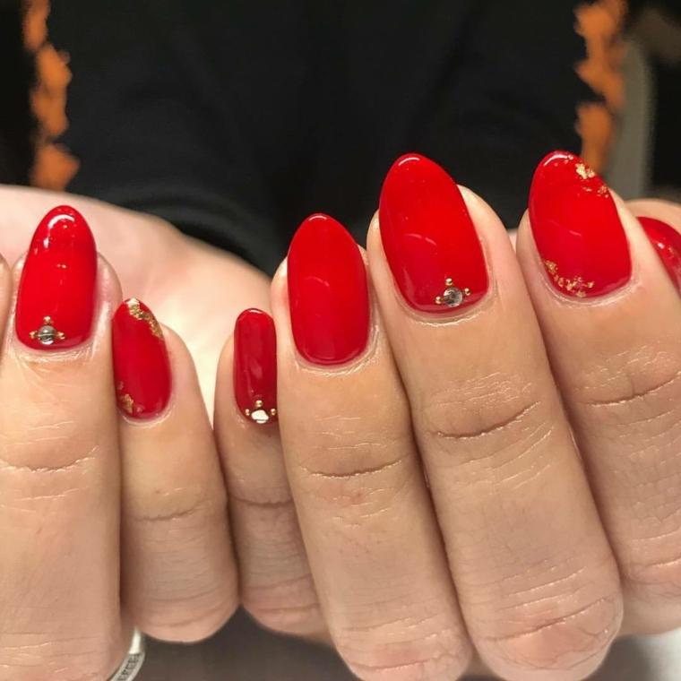 unghie a mandarlo dipinte con uno smalto rosso extra lucido e decorate finemente