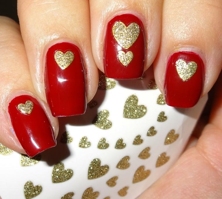 unghie laccate con smalto rosso e decorate con dei cuoricino dorati