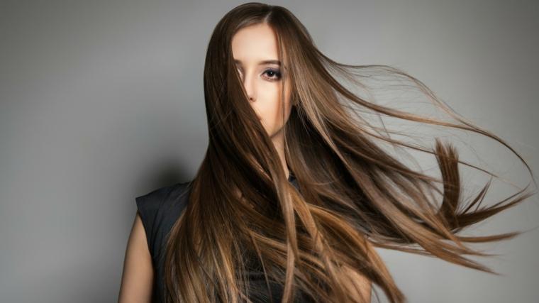 Colore castano per capelli lunghi con un taglio pari, la riga è di lato