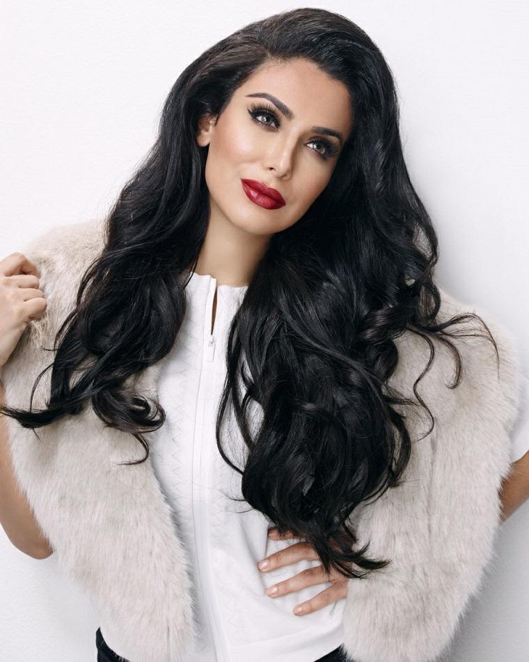 I capelli neri sono sempre eleganti con la giusta acconciatura, donna truccata con capelli mossi e lunghi