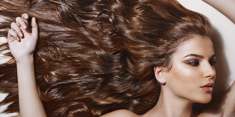 Donna con i capelli di colore castano intenso con ricci e scalature leggere